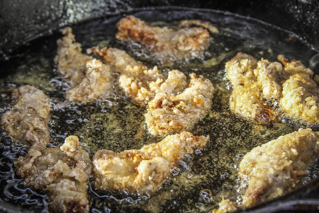Season the legs with white pepper, then coat with cornstarch and pan-fry until golden, crispy brown.