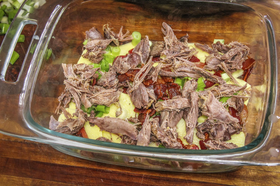 Layer the sliced potatoes and other ingredients in the casserole dish.