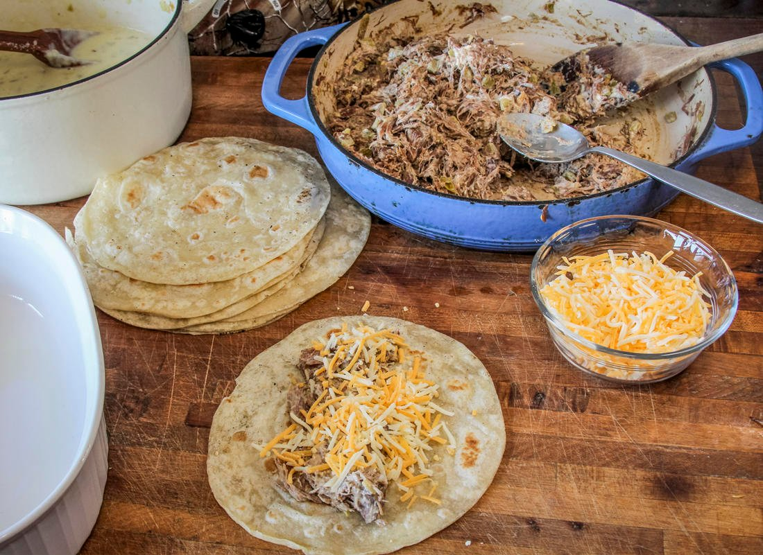 Assemble the enchiladas by filling the tortillas with meat and a bit of shredded cheese.