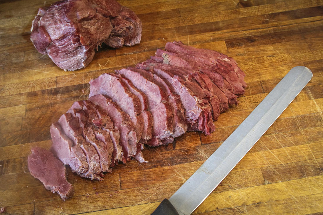 Braise the corned venison in beef or venison stock, then cool and slice for casserole.