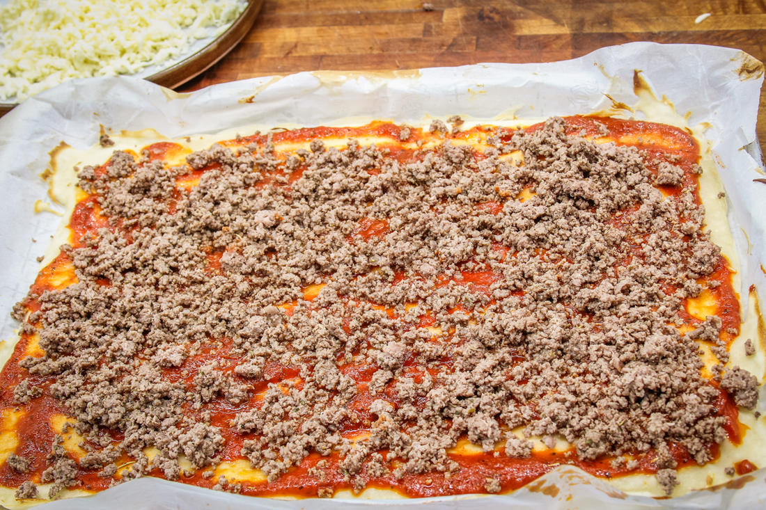 Sprinkle the seasoned browned venison evenly over the pizza crust.