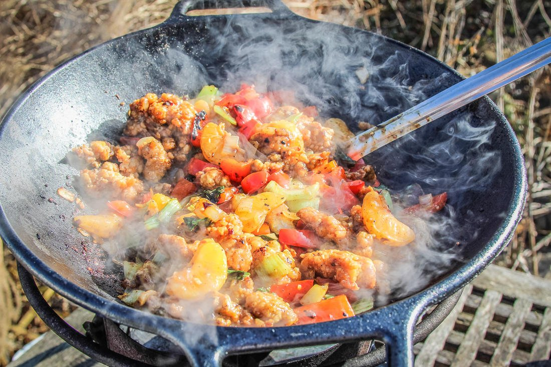 In a wok over the extreme high heat of an outdoor gas burner, the stir-fry cooks in minutes.