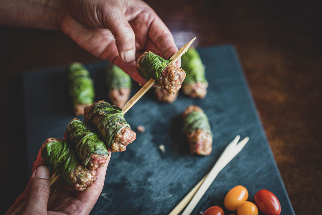 Add the meat rolls to a soaked bamboo skewer. Image by Grit Media
