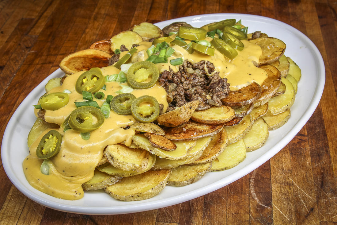 Form a shallow bowl with the potatoes, then fill it with venison and beer cheese sauce.
