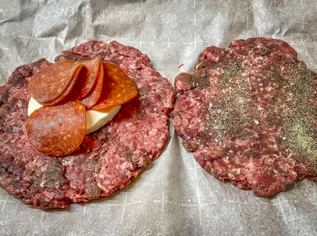Form two thin patties, season, add the pepperoni and cheese, then seal together to form a stuffed burger.