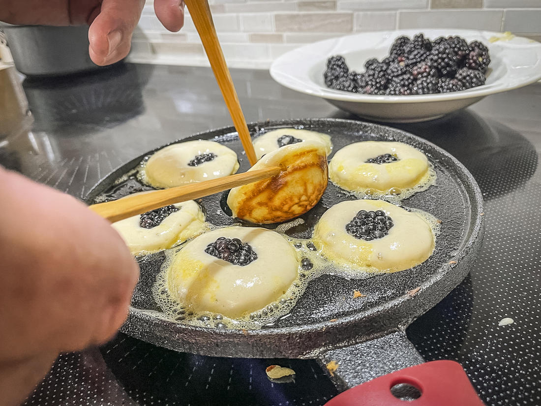 Use traditional wooden skewers, or a set of chopsticks, to flip the aebleskivers in the pan.