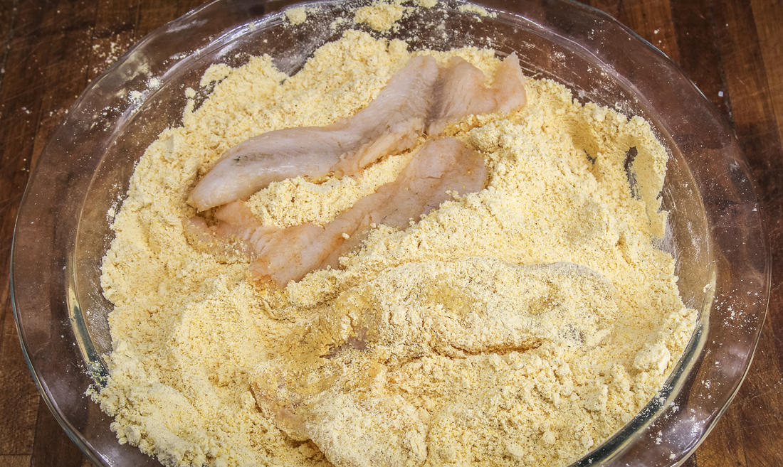 Dredge the fish in seasoned cornmeal.