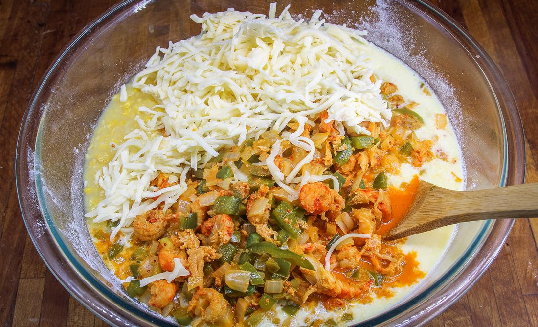 Stir the wet ingredients, corn, cheese, and cooked crawfish mixture into the dry ingredients.