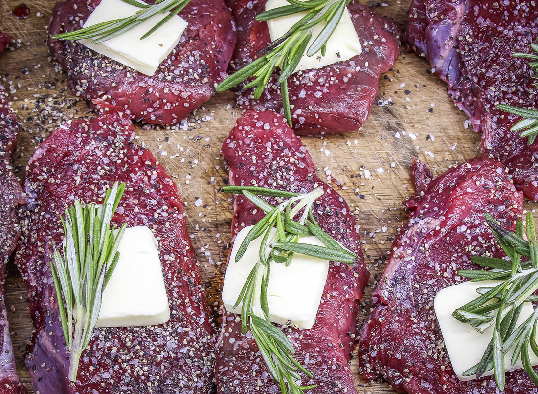 Season each steak with salt and pepper, then top with a pat of butter and a sprig of rosemary.