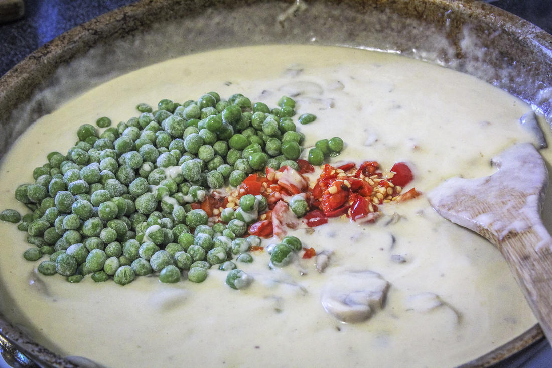 Stir the frozen peas and diced peppers into the mushroom cream sauce.