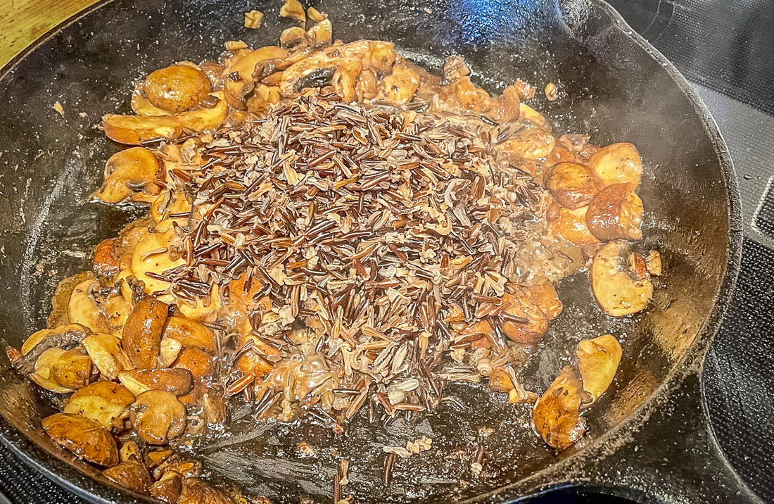 Sauté the mushrooms, then add the cooked wild rice to the pan before deglazing with cider.