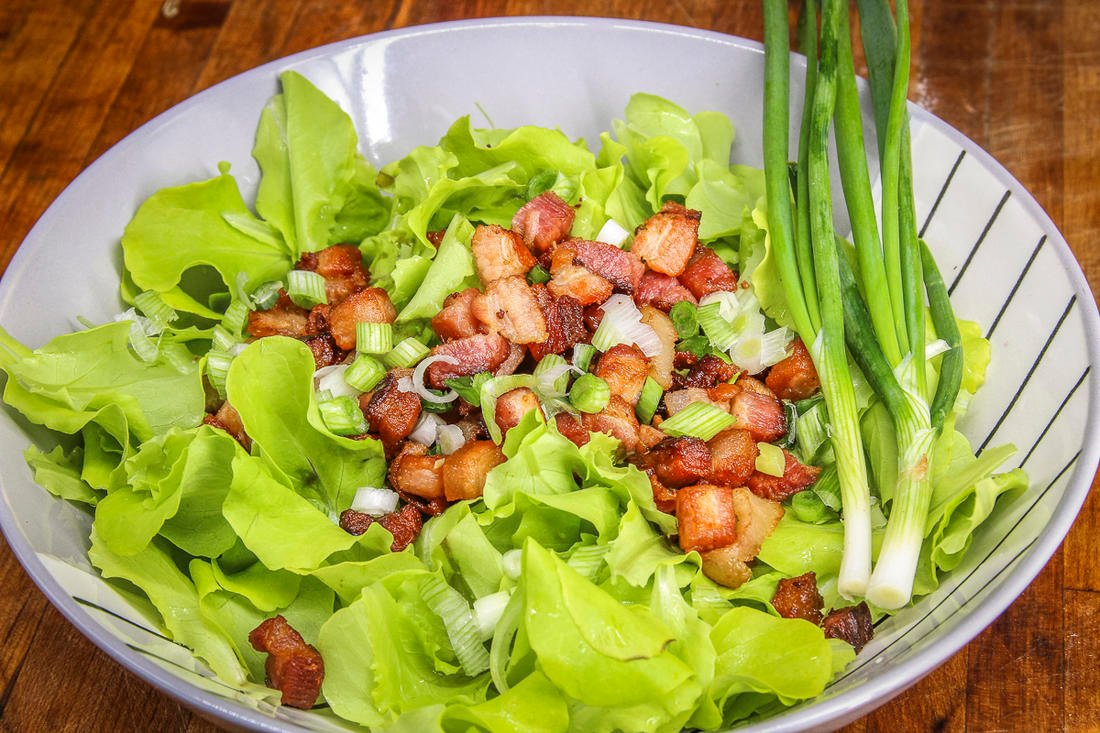 Top the salad with crispy bacon bits and diced green onions.
