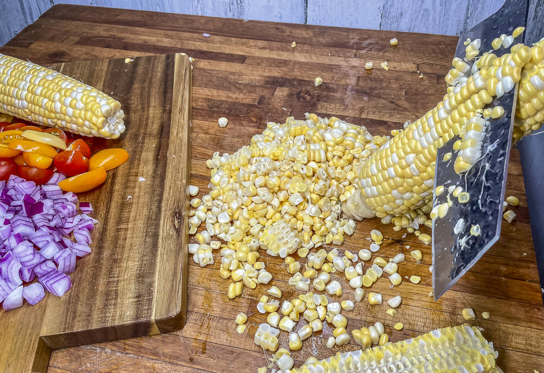 Slice the fresh sweet corn from the cob.