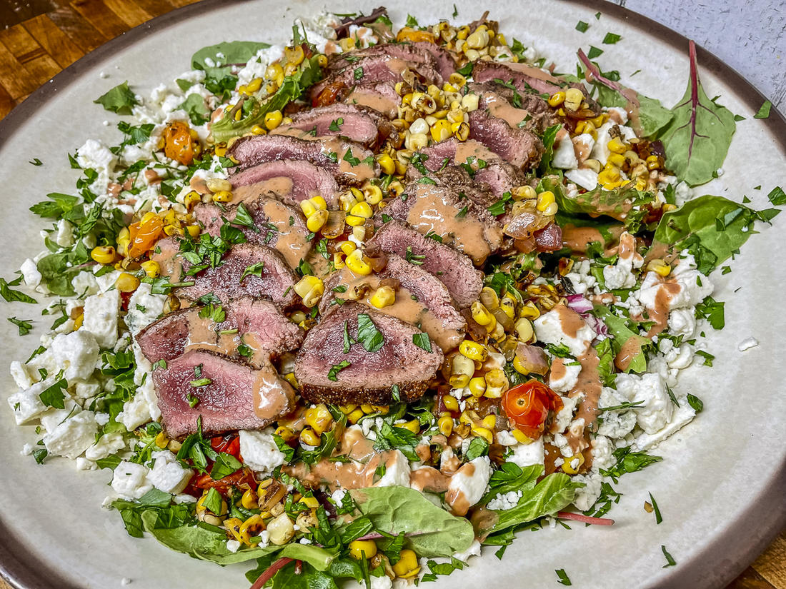 Layers of grilled sweet corn, red onion, and fresh tomatoes get layered over crisp salad greens and topped with thinly sliced backstrap.