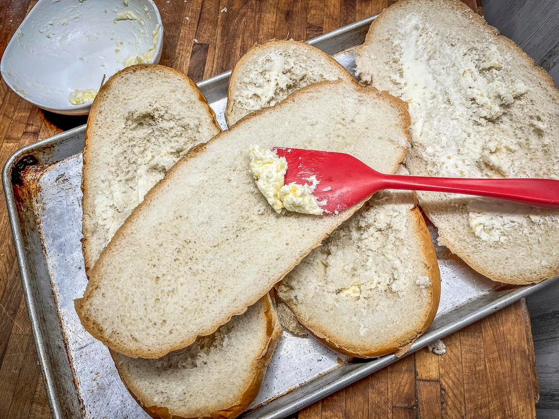 Spread the softened garlic butter over the bread, then toast.