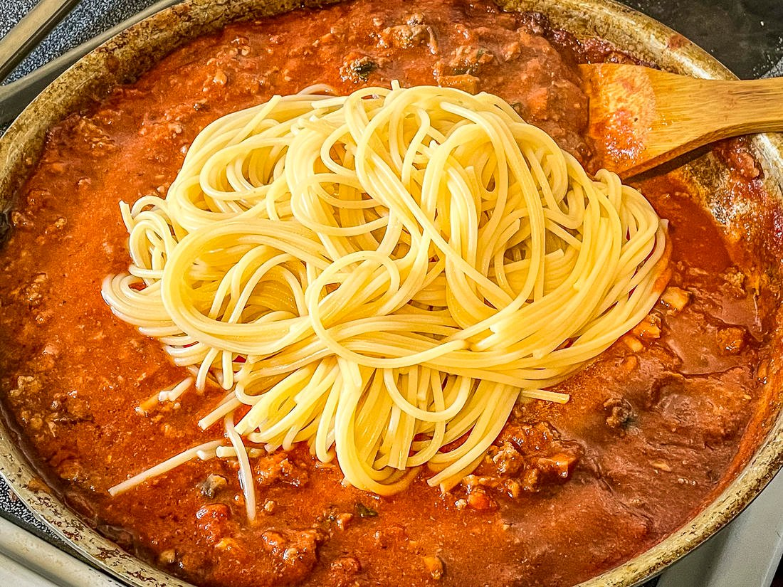 Stir the cooked spaghetti into the sauce.