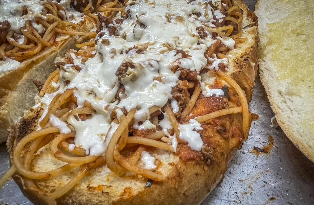 Top the spaghetti with shredded mozzarella and run it under the broiler to melt.