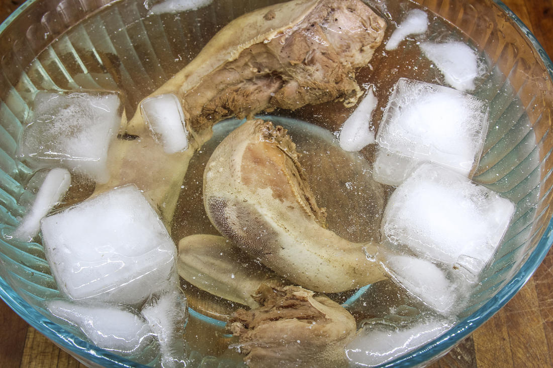 Submerge the tongues in cold water to stop the cooking process, then peel away the skin.