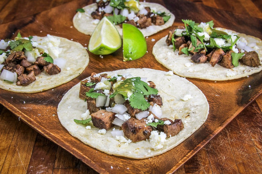 Serve the tongue on tortillas with traditional street taco toppings.