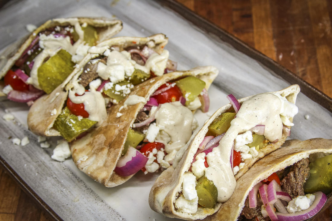 Fill the pita pockets with grilled venison, tomato pickle salad, and feta cheese, then drizzle on tahini sauce before serving.
