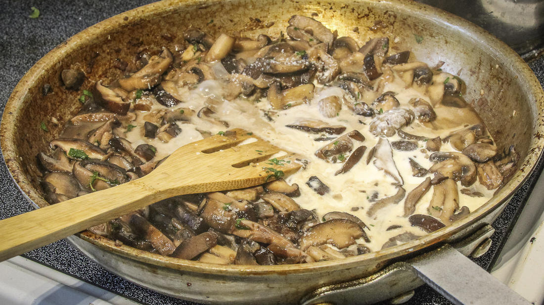 Add the wine and stock to the sautéed mushrooms, reduce the liquid to intensify flavor, then stir in the stock.