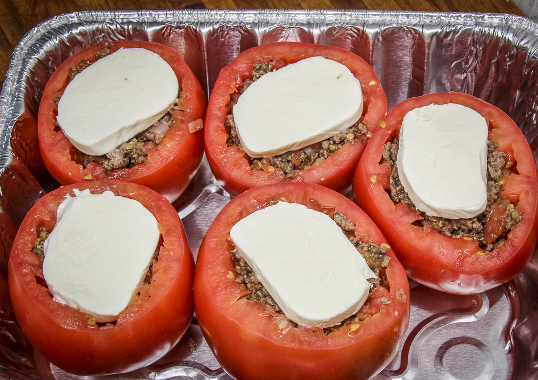Fill the tomatoes with the venison mixture, then top with a slice of fresh mozzarella cheese.