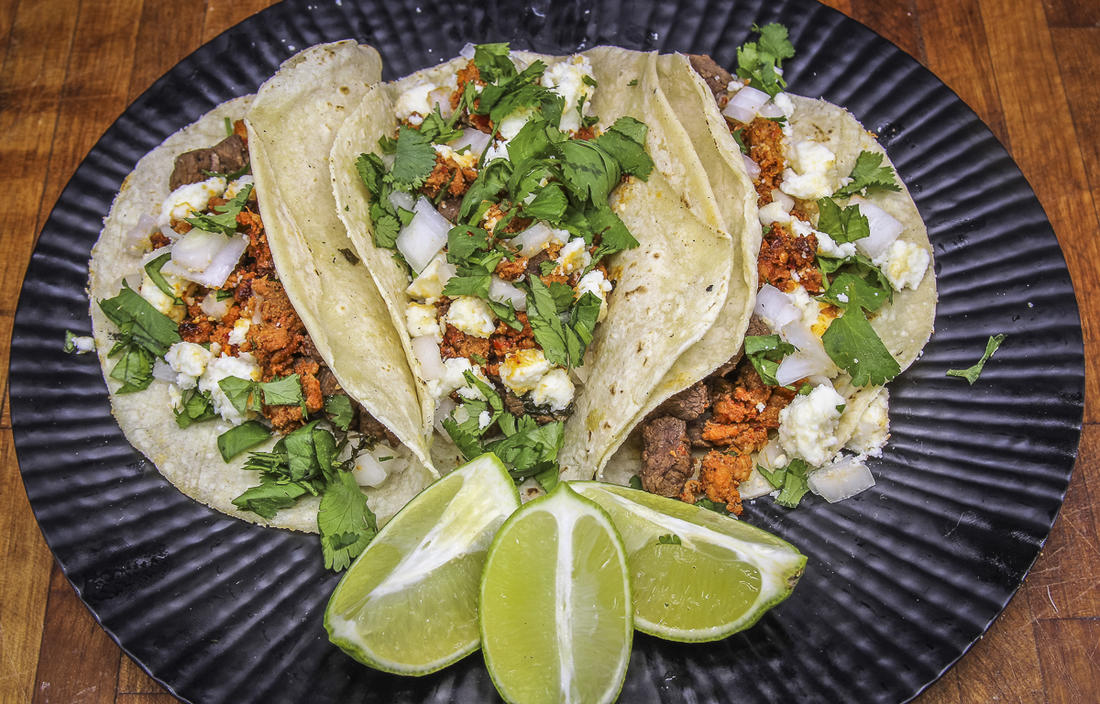 Pile the tacos with venison and chorizo, then top with diced onion and fresh cilantro.