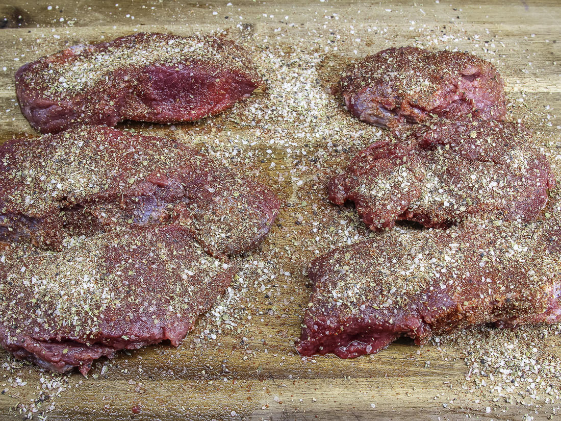 Apply the seasoning blend to both sides of the backstrap steaks.