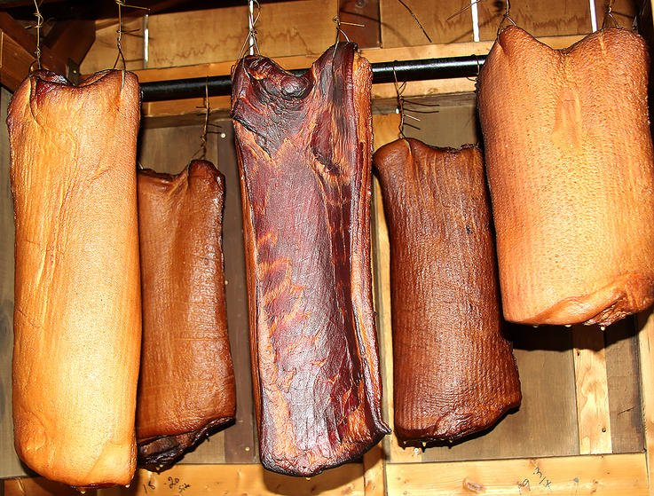 Apply the smoke through either a hot smoke on a smoker, or as a cold smoke in a smokehouse.