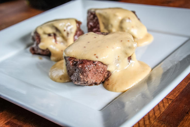 Backstrap medallions topped with beer cheese sauce.